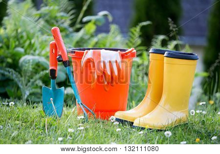 Gardening equipment and yellow rubber boots on grass field with greenery in background. Gardening concept