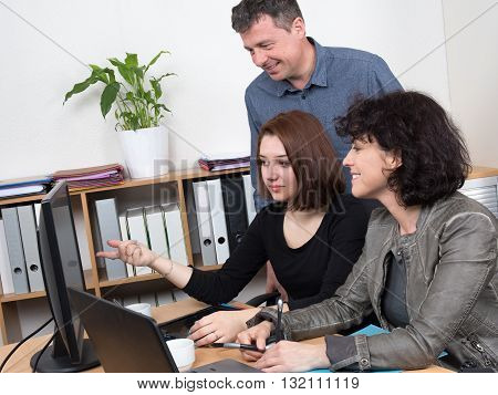 Smiling And Happy Business Team In Front Of Laptop