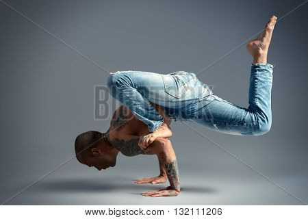 A man doing yoga exercises. Studio shot over gray background.