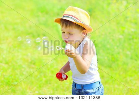 Little Child  Boy Blowing Soap Bubbles Outdoors In Summer Day
