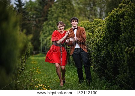 Happy And Smiled Couple Running In Love At Park Garden. Stylish Man At Velvet Jacket And Girl In Red