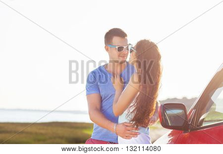 Young smile couple romantic standing by the car at the summer background