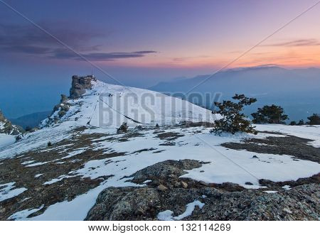 snow-covered mountains and rocks at purple sunset with clouds on sky