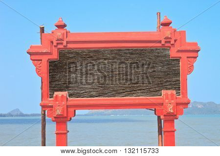 an image of a signpost situated against a wall at a sunny beach