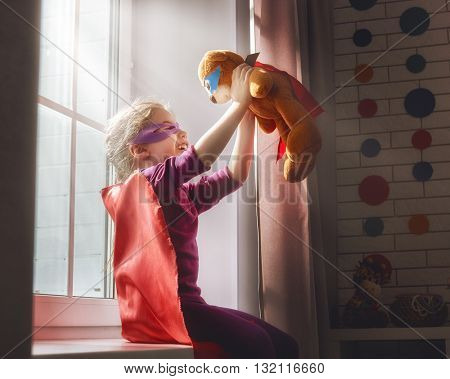 Little child girl plays superhero. Child plays with her friend a Teddy bear. Girl power concept.