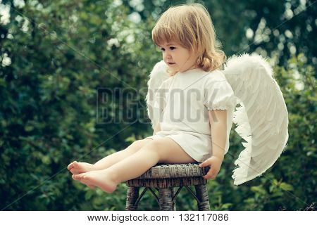 Little angle boy on the chair. Cute angel is ready to fly away