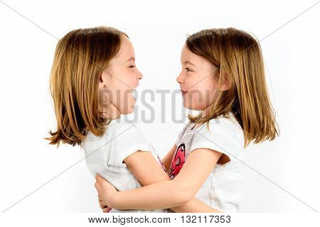 Twin Girls Are Looking At Eachother And Smiling.