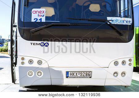 HERAKLION GREECE - APRIL 28 2016: Modern white tourist bus with logo of Anex Tour company and DeltaNet transport parked at Heraklion Airport N. Kazantzakis Crete Greece