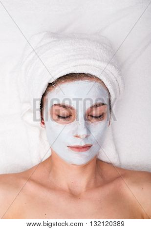 Portrait of young woman with cosmetic beauty facial mask spa treatments and closed eyes