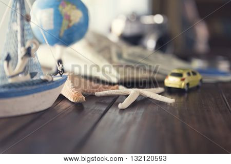 Map, Globe, Ship And Car Figurine, Starfish, Banknote, Camera On Wooden Table For Use As Traveling C