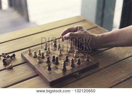 Hand Holding Pawn Of Chessboard Game On Wooden Table, Vintage Tone And Selected Focus