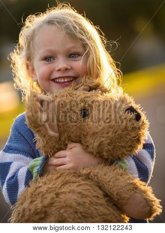 close up of a cute smiling 4 year old caucasian child hugging his big brown teddy bear backlit by the setting sun