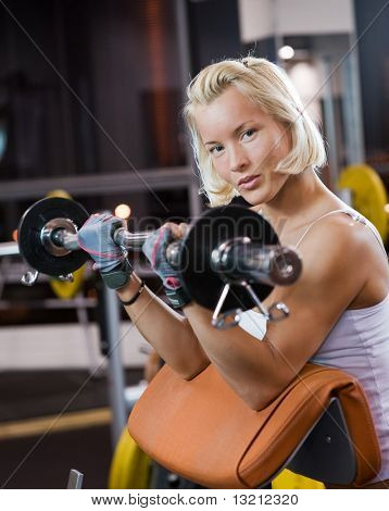 Strong beautiful woman lifting heavy weights