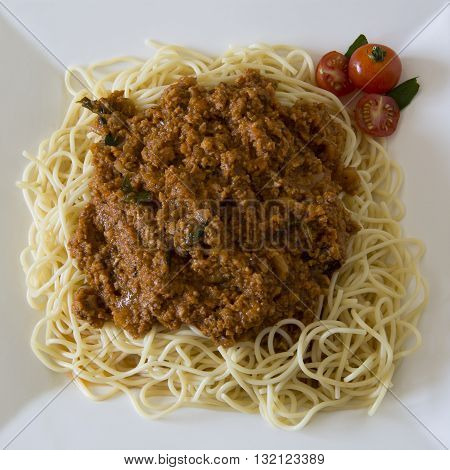 Vegetarian Spaghetti Bolognaise with minced soya (garnished with cherry tomatoes and basil leaves)