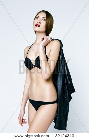 Caucasian beautiful woman in black underwear with black jacket on white isolated