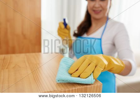 Cropped image of woman cleaning surface with detergent