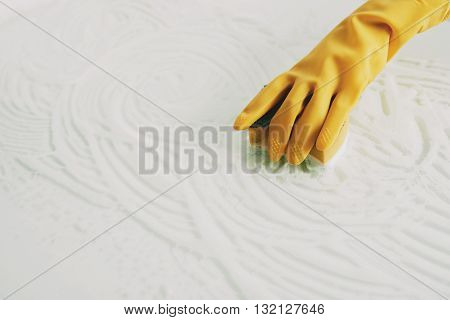 Hand of woman cleaning surface with sponge and foam