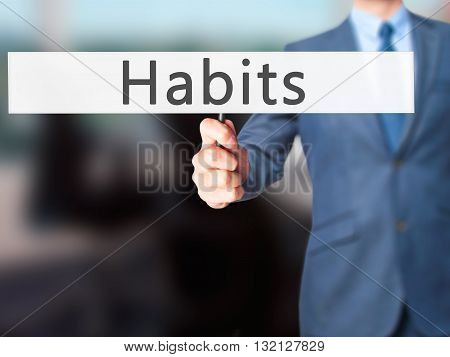 Habits - Businessman Hand Holding Sign