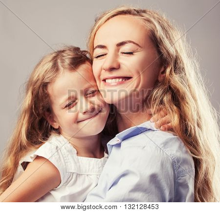 Mother with little girl. Parent with child. Happy family clouse up