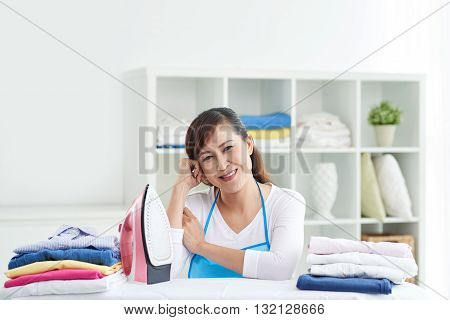 Pretty middle-aged woman ironing clothes after washing