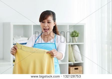 Shocked Asian housewife looking at shirt in her hands