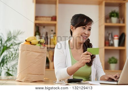 Cheerful Vietnamese housewife ordering fresh food online