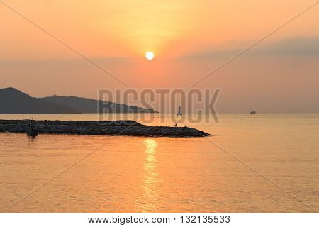 sunrise at sea. variety of colors and hues of the rising sun Reflections on the sea. There are boats and bicycles on a small rocky island.