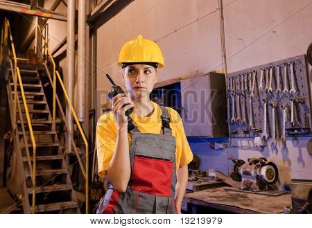 Female factory worker talking on the radio phone