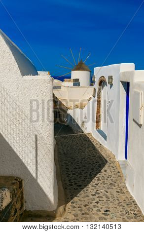 Picturesque view of empty streer, white and blue houses and windmill in Oia or Ia, island Santorini, Greece