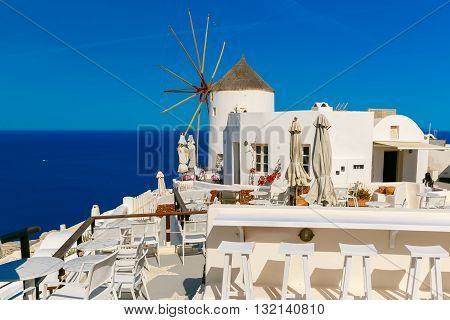 Picturesque view of windmill, empty restaurant and white houses in Oia or Ia on the island Santorini, Greece
