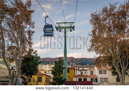 Cable car is going over the old town of Funchal. Touristic district of the city, sunset warm light and mountain range on the background. Funchal, Madeira island, Portugal.