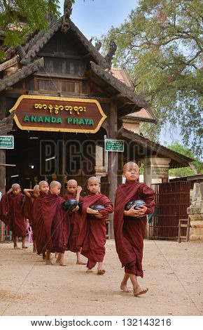 Bagan, Myanmar - April 22 2016 : Little Buddhist monks walking in front of Gate of Ananda temple