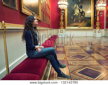 young woman sitting in an art gallery or museum and looks at paintings (Russia St. Petersburg The museum Hermitage)