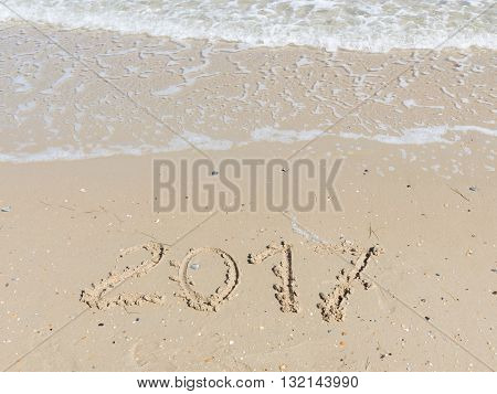2017 inscription on a light yellow sand fines with small stones and fragments of shells on the sandy beach and a wave of clean sea water with white foam