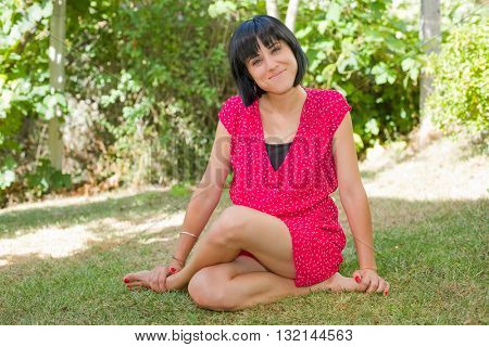 young casual woman posing seated, smiling at the camera, outdoors