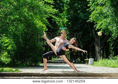 Contemporary dance. Man and woman in passionate dance pose in park. Young couple dancing modern dance. Girl doing splits. Man with naked torso. Old park, trees in background.