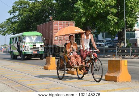 Yangon Myanmar - April 25 2016 : Guy riding Tricycle taxi for lady in Yangon