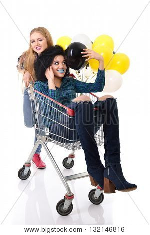 Two happy hipster girls have fun in supermarket's trolley with balloons over white background