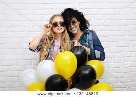 Two happy hipster girls in sunglasses have fun with balloons over white wall background.