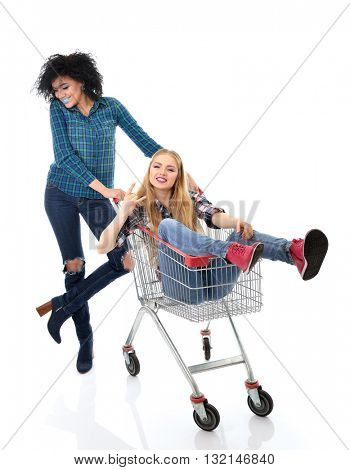 Two happy hipster girls have fun in supermarket's trolley over white background