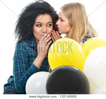 Two happy hipster girls talking secrets each other with balloons over white background