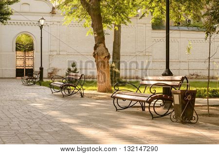 Benches tree lamps in park. Landscape. The place of shooting - city park. Time - summer morning. Outdoors. Horizontal. In the foreground - a bench. Side view. On the average plan - a tree. On a distance shot - a bench a lamp and a brick wall with gate.