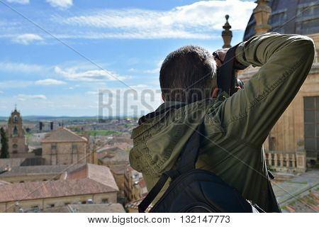 Professional photographer taking photo outdoor in ancient spanish city Salamanca, working.