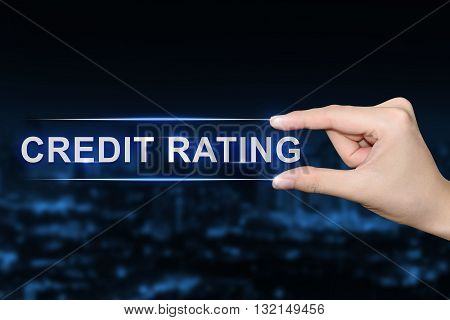 hand pushing credit rating button on blurred blue background