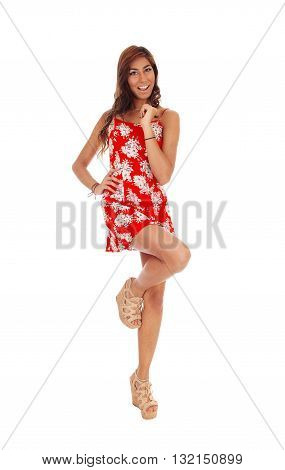 A lovely happy young woman standing in front on one leg in a red dress smiling isolated for white background.