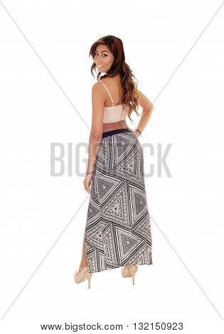 A beautiful young woman in a long skirt and short top standing from the back looking over shoulder isolated for white background.