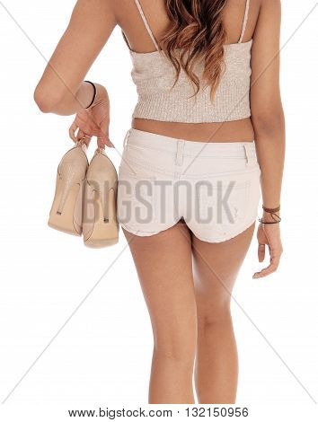 A close-up image of a slim young woman in shorts from the back holding her heels isolated for white background.