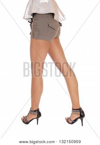 A closeup image of the long legs and bottom of a young woman in olive shorts and high heels isolated for white background.