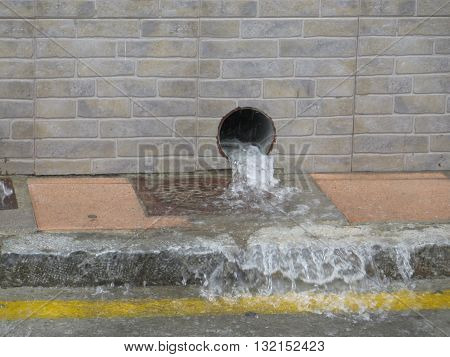 water gushing out of Rainwater drain pipe during torrential downpour