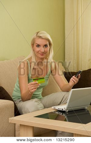 Happy young woman using credit card to make online purchase
